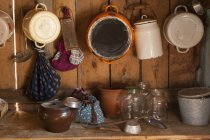 Traditional wood kitchen with saucepans, jars and utensils on shelf — Stock Photo