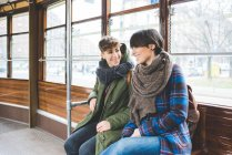 Two women sisters sitting on cable car, smiling — Stock Photo