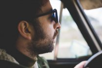 Close up of mid adult man driving and  wearing sunglasses — Stock Photo