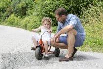 Дівчина їзда триколісний з батьком на сільській дорозі — стокове фото