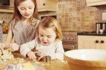 Девочка и старшая сестра делают выпечку в форме звезды за кухонным столом — стоковое фото