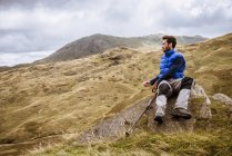 Young male hiker looking out over landscape, The Lake District, Cumbria, UK — Stock Photo