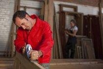 Carpenter using plane at carpentry — Stock Photo
