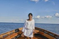 Молода жінка на човні в блакитному океані — стокове фото