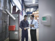 Arbeiter und Büroleiter diskutieren Energieverbrauch neben Heizkessel in Fabrik — Stockfoto