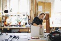 Joven artesana comprobando componente en taller de órgano de tubería - foto de stock