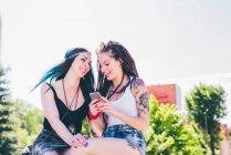 Zwei junge Frauen lachen über Smartphone Texte in städtische Wohnsiedlung — Stockfoto