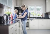 Mother and son baking together, stirring mixture in mixing bowl — Stock Photo