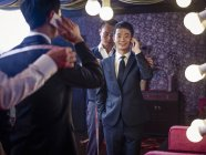 Young man trying on suit in traditional tailors shop — Stock Photo