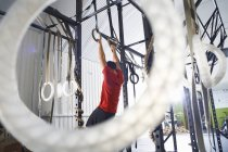 Rear view of athlete doing workout on gymnastic rings — Stock Photo