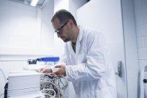 Assistant de laboratoire travaillant sur des équipements professionnels — Photo de stock