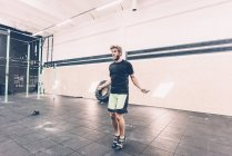 Young male cross trainer training with skipping rope in gym — Stock Photo
