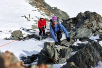 Mountaineer climbing up snow covered mountain, Saas Fee, Switzerland — Stock Photo