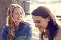 Zwei schöne Frauen unterhalten sich im Sonnenschein — Stockfoto