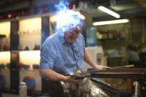 Glassblower in workshop forming molten glass on blowpipe — Stock Photo
