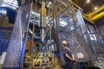 Ingeniero de tratamiento térmico de piezas de acero en horno de inducción en la fábrica de ingeniería - foto de stock