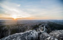 Young male hiker on top of rock formation at sunset — Stock Photo