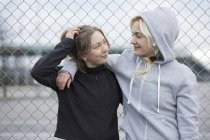 Две счастливые подруги-бегуньи у ограды — стоковое фото