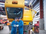Инженеры, использующие цифровой планшет в ремонте грузовиков — стоковое фото