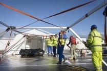Equipe de resposta de emergência Trabalhadores da equipe que erguem centro de controle de barraca — Fotografia de Stock