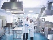 Travailleurs en discussion à l'intérieur de l'usine pharmaceutique — Photo de stock