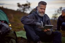 Мандрівні з використанням цифрової планшета в таборі, Лапландія, Фінляндія — стокове фото