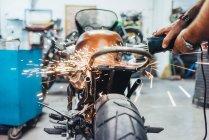 Mature man, working on motorcycle in garage — Stock Photo