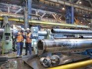 Engineers checking steel tubes in engineering factory — Stock Photo