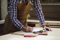 Обрезанный снимок зрелого мастера, делающего заметки в органной мастерской — стоковое фото