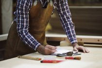 Cropped shot of mature craftsman making notes in organ workshop — Stock Photo