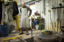 Male foundry worker putting on aluminium coated apron in bronze foundry — Stock Photo