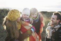 Середині пара дорослі в піщані дюни з сином і дочкою загорнутий у ковдру — стокове фото