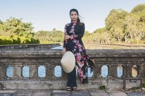 Woman wearing traditional Ao Dai dress at the old imperial city in Hue, Vietnam — Stock Photo