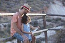 Pai e filha sentados na cerca leitura nota, Almeria, Andaluzia, Espanha — Fotografia de Stock
