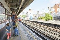 Madre e hijo caucásicos mirando el mapa del metro en la plataforma ferroviaria, Londres, Reino Unido - foto de stock