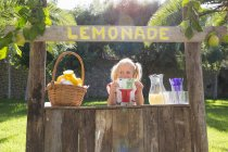Portrait of girl on lemonade stand holding up one hundred euro note — Stock Photo