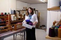 Frau in Webstube hält Behälter mit Garnen — Stockfoto