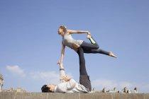 Hombre y mujer practicando yoga acrobático en la pared - foto de stock