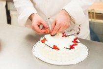 Cropped image de Baker décoration gâteau aux fraises — Photo de stock
