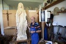 Escultor de pé com figura de madeira — Fotografia de Stock