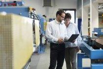Коллеги по работе проверяют информацию о ноутбуке на заводе — стоковое фото