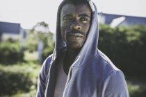 Portrait of man wearing hooded top looking away — Stock Photo
