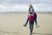 Uomo donando donna porcellino indietro, Brean Sands, Somerset, Inghilterra — Foto stock