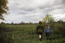 Mother and daughter holding hands walking in meadow, Lakefield, Ontario, Canada — Stock Photo