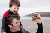 Padre che tiene granchio con figlio — Foto stock