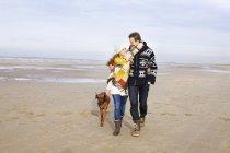 Casal adulto médio e cão passeando na praia, Bloemendaal aan Zee, Países Baixos — Fotografia de Stock