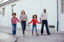 Parents and two children walking and holding hands on street — Stock Photo