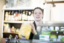 Portrait of young female shop assistant at corner shop counter — Stock Photo