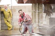 Pintor masculino navio limpeza de casco de navio com arruela de pressão no quintal de pintores de navio — Fotografia de Stock