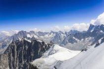 Snowcapped гори з хмар під Синє небо — стокове фото